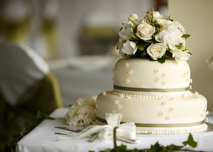 A white wedding cake decorated by Baker X.